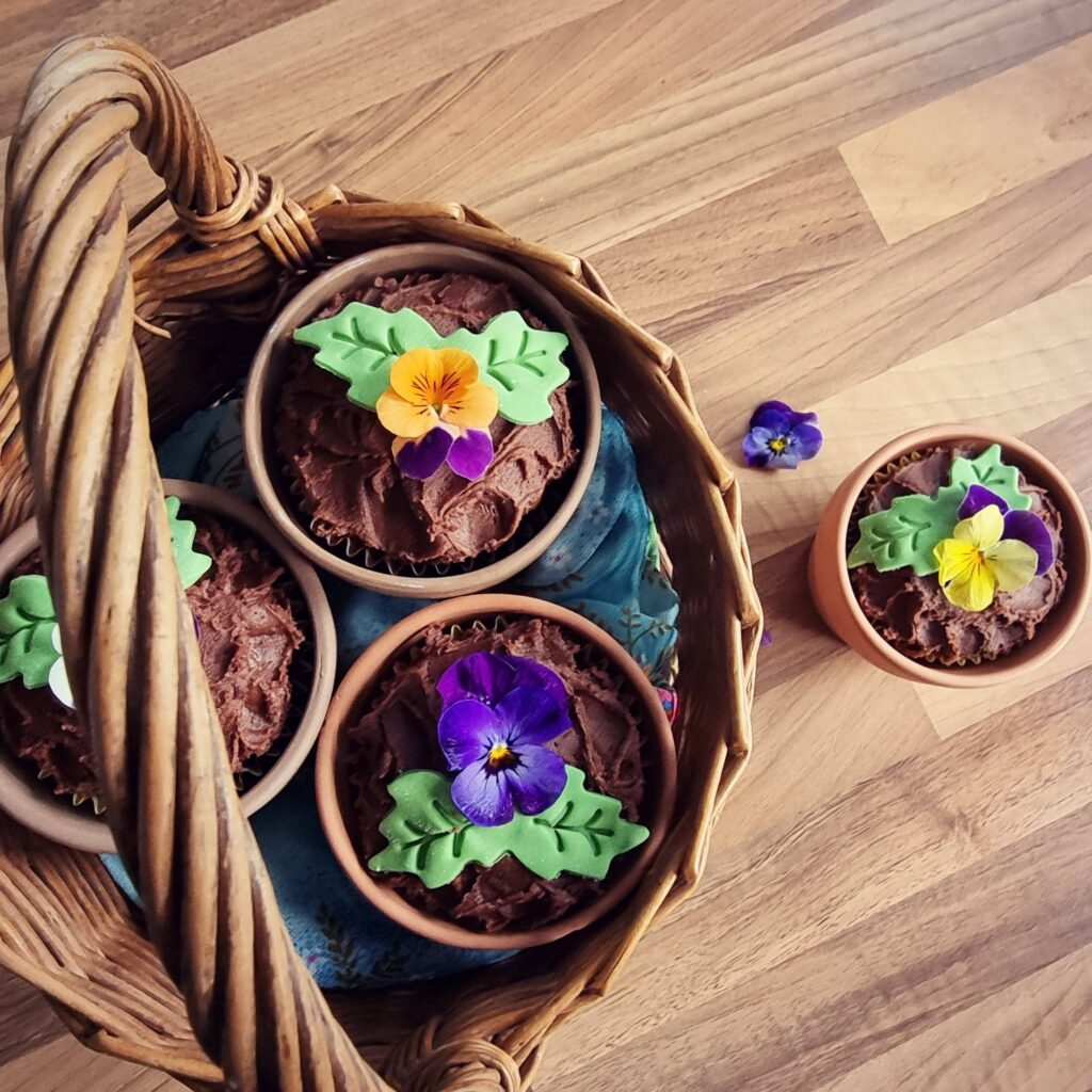 Cupcakes made to look.like plants sit in plant pots. There are three pots on a wicker basket and one on the worktop