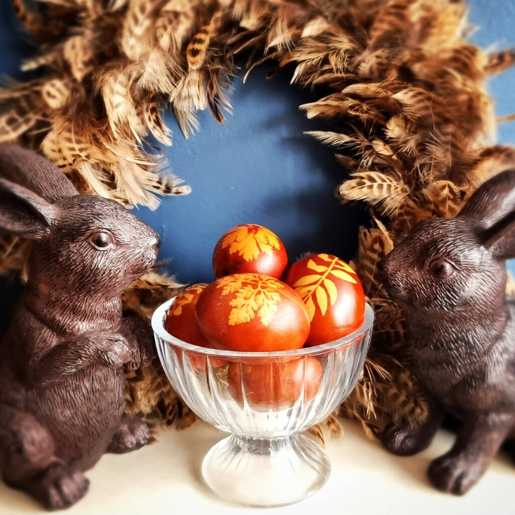 Brown eggs with leaf silhouettes, in a bowl with a feathered wreath behind